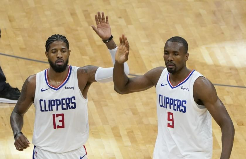 Los Angeles Clippers Paul George, left, and Serge Ibaka prepare to give high-five to teammates.