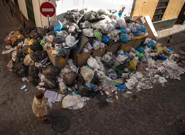 A pedestrian passes a pile of garbage during the 10th day of the Seville waste disposal strike on February 6, 2013 in Seville, Spain. Workers are striking over demands they take a 5% pay cut and extend their working week to 37.5 hours. (Photo by Denis Doyle/Getty Images)