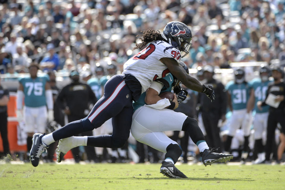 FILE - In this Oct. 21, 2018, file photo, Jacksonville Jaguars quarterback Cody Kessler is sacked by Houston Texans linebacker Jadeveon Clowney (90) during the second half of an NFL football game in Jacksonville, Fla. Two people with knowledge of the deal say the Seattle Seahawks are on the verge of acquiring Clowney from the Texans. Such a move would bolster one of Seattle's biggest needs heading into the season. The people spoke to The Associated Press on condition of anonymity Saturday because the deal is still pending a physical and had not been completed. Seattle reportedly is sending a third-round pick and two players back to Houston. (AP Photo/Phelan M. Ebenhack, File)