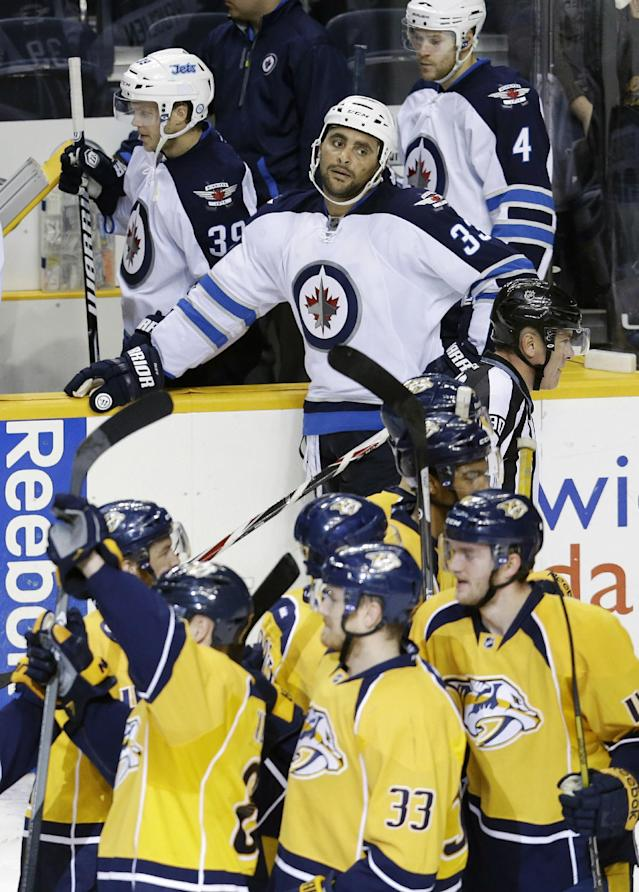 Winnipeg Jets defenseman Dustin Byfuglien (33) watches as Nashville Predators players celebrate after the Predators beat the Jets 3-2 in overtime at an NHL hockey game on Thursday, Oct. 24, 2013, in Nashville, Tenn. (AP Photo/Mark Humphrey)