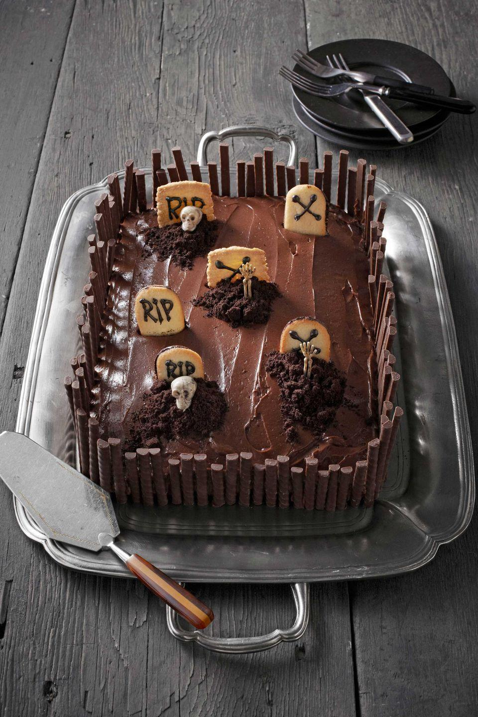 """<p>The key to this mini-cemetery is the array of tombstones fashioned from Pepperidge Farm's Milano and Bordeaux cookies.</p><p><strong>Step 1:</strong> Bake chocolate cake of your choosing and frost with your favorite chocolate frosting.</p><p><strong>Step 2:</strong> Pipe """"X"""" and """"RIP"""" in chocolate icing on cookies. Push into cake and crumble chocolate wafers to make """"dirt.""""</p><p><strong>Step 3:</strong> Surround edges of the cake with chocolate wafers.</p><p><strong>Step 4:</strong> Insert plastic skeletons into the """"dirt.""""</p><p><strong><a href=""""https://www.countryliving.com/food-drinks/g217/basic-vanilla-and-chocolate-cake-recipes/"""" rel=""""nofollow noopener"""" target=""""_blank"""" data-ylk=""""slk:Get a basic cake recipe"""" class=""""link rapid-noclick-resp"""">Get a basic cake recipe</a>.</strong></p><p><strong><a href=""""https://www.countryliving.com/food-drinks/recipes/a37728/rich-chocolate-frosting-recipe/"""" rel=""""nofollow noopener"""" target=""""_blank"""" data-ylk=""""slk:Get a recipe for chocolate frosting"""" class=""""link rapid-noclick-resp"""">Get a recipe for chocolate frosting</a>.<br></strong></p>"""