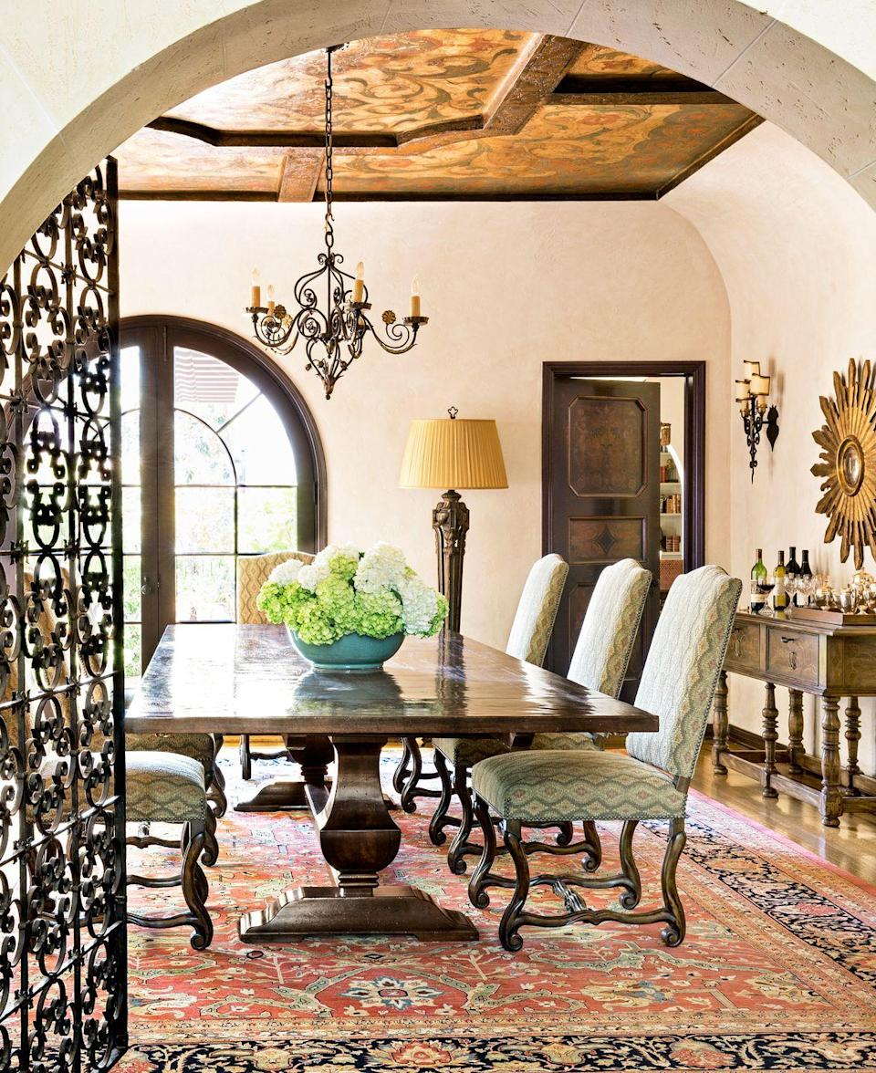 <p>In this Mediterranean-style dining room, the elaborate iron wrought door and chandelier, imposing dining table, and bold antique carpet are only surpassed in intricate beauty by the stylized ceiling of exposed beams framing a mural. Because the carpet makes such an eye-catching impression, the ceiling does a nice job of containing the space for a full jewel box effect. The thoughtful design of the space ensures a truly magical setting for intimate dining and conversation. </p>