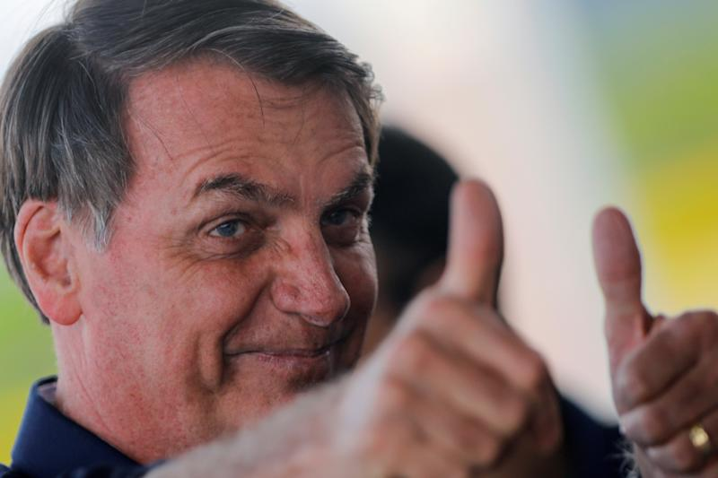 Brazil's President Jair Bolsonaro reacts while answering questions from journalists outside the Alvorada Palace in Brasilia, Brazil December 27, 2019. REUTERS/Adriano Machado