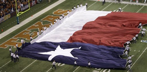 The Texas flag is run on to the field prior to the Alamo Bowl NCAA football game between Oregon State and Texas, Saturday, Dec. 29, 2012, in San Antonio. (AP Photo/Eric Gay)