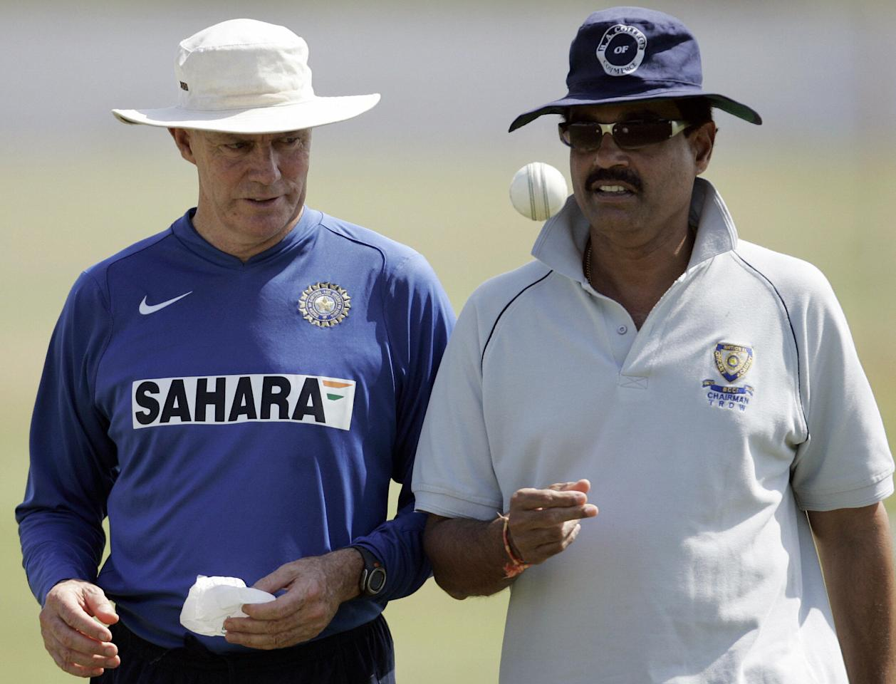 Ahmedabad, INDIA:  Chief Indian cricket selector Dilip Vengsarkar (R) tosses the ball while talking to coach Greg Chappell (L) during a practice session at the Sardar Patel Stadium in Ahmedabad, 25 October 2006.  India will play their next match of the ICC Champions Trophy 2006 against West Indies on October 26.       AFP PHOTO/ MANAN VATSYAYANA  (Photo credit should read Manan Vatsyayana/AFP/Getty Images)