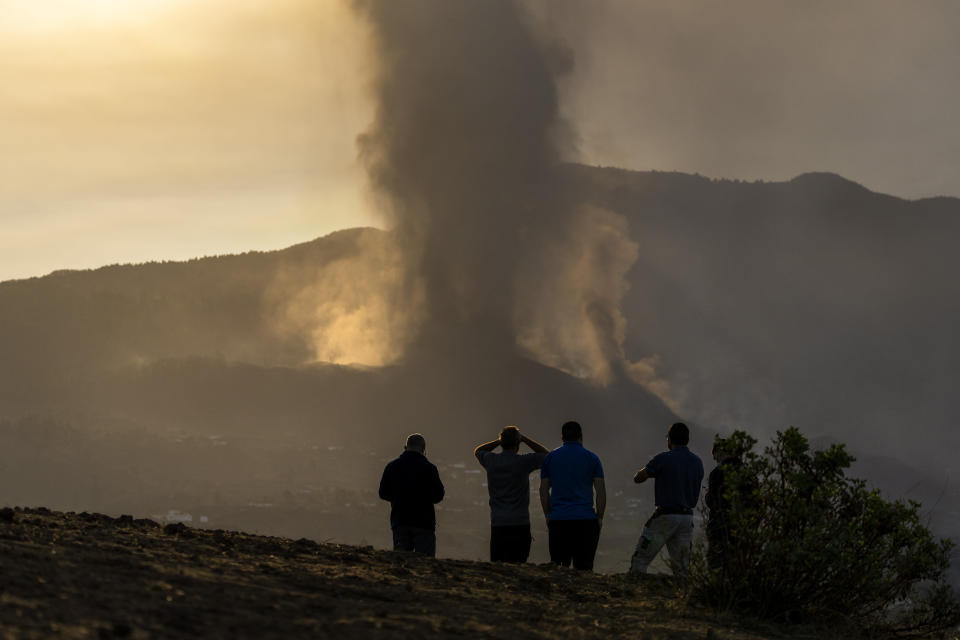Residents watch from a hill as lava continues to flow from an erupted volcano, on the island of La Palma in the Canaries, Spain, Friday, Sept. 24, 2021. A volcano in Spain's Canary Islands continues to produce explosions and spew out lava, five days after it erupted. Two rivers of lava continue to slide slowly down the hillside of La Palma on Friday. (AP Photo/Emilio Morenatti)