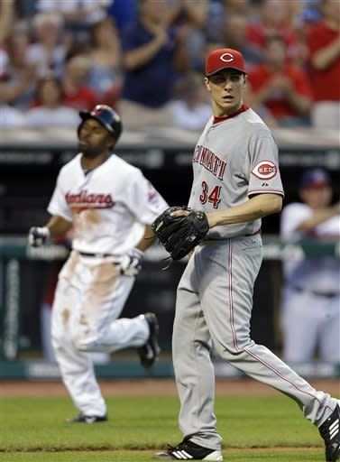 Cincinnati Reds starting pitcher Homer Bailey (34) heads to back up the plate as Cleveland Indians' Michael Bourn scores on a single by Jason Kipnis in the fourth inning of a baseball game Thursday, May 30, 2013, in Cleveland. (AP Photo/Mark Duncan)