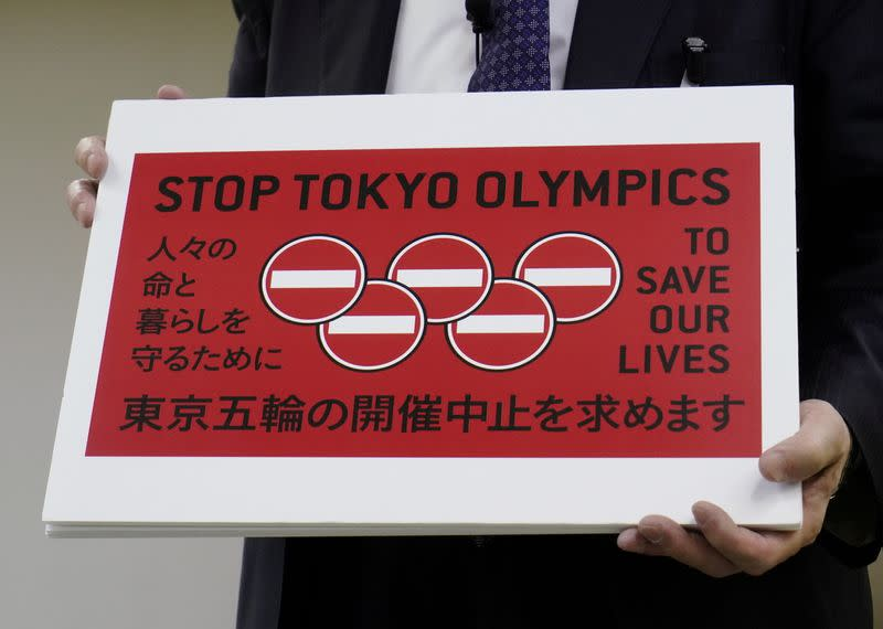 Lawyer Kenji Utsunomiya shows off a placard during a news conference after he and anti-Olympics petition organizer to submit a petition calling for the Tokyo 2020 Olympics to be cancelled in Tokyo