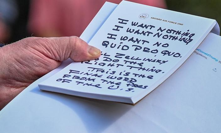 President Trump holds what appears to be handwritten notes after watching testimony by Gordon Sondland as he speaks to reporters on the South Lawn of the White House on Wednesday. (Photo: Erin Scott/Reuters)