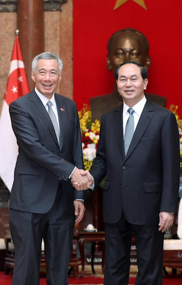 Singapore's Prime Minister Lee Hsien Loong (L) and Vietnamese President Tran Dai Quang (R) shake hands at the Presidential Palace in Hanoi, Vietnam 23 March 2017. REUTERS/Luong Thai Linh/Pool