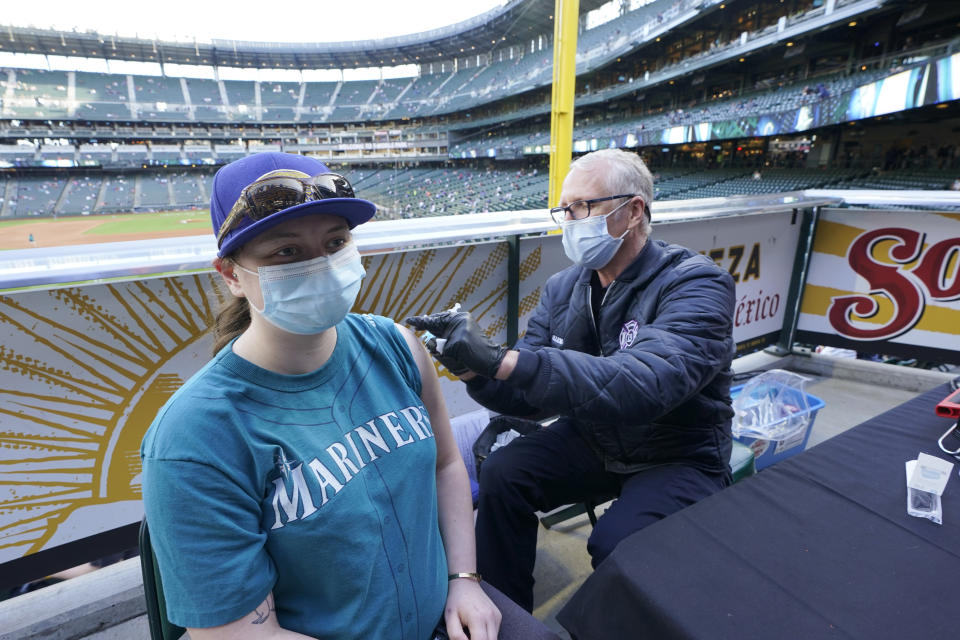 Bill Allemann, right, an EMT and firefighter with the Seattle Fire Dept., gives a Johnson & Johnson COVID-19 vaccine shot to a Seattle Mariners fan, Tuesday, May 4, 2021, during a clinic held at T-Mobile Park before a baseball game between the Mariners and the Baltimore Orioles in Seattle. The Mariners will be offering free COVID-19 vaccines to eligible fans at three locations in the ballpark during upcoming home games. (AP Photo/Ted S. Warren)