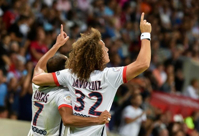 Paris Saint-Germain's midfielder Lucas Moura (L) celebrates with defender David Luiz after scoring during a French Ligue 1 football match against Lille on August 7, 2015 at the Pierre Mauroy Stadium in Villeneuve d'Ascq