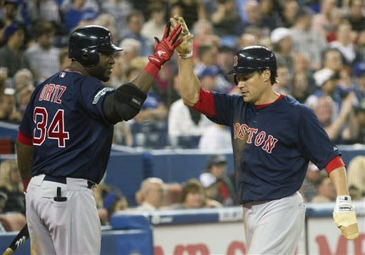 Boston Red Sox's Scott Podsednik, right, celebrates with teammate David Ortiz, left, after scoring a run against the Toronto Blue Jays during eighth-inning AL baseball game action in Toronto, Friday, June 1, 2012. (AP Photo/The Canadian Press, Nathan Denette)