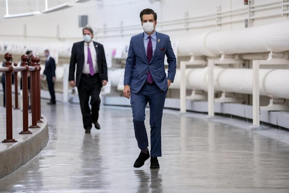 Matt Gaetz in a suit wears a protective mask while walking through the Canon Tunnel
