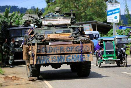 A tricycle cab drives past an armoured personnel carrier parked along a main road in Pantar village, Lanao Del Norte, Philippines June 21, 2017. REUTERS/Romeo Ranoco
