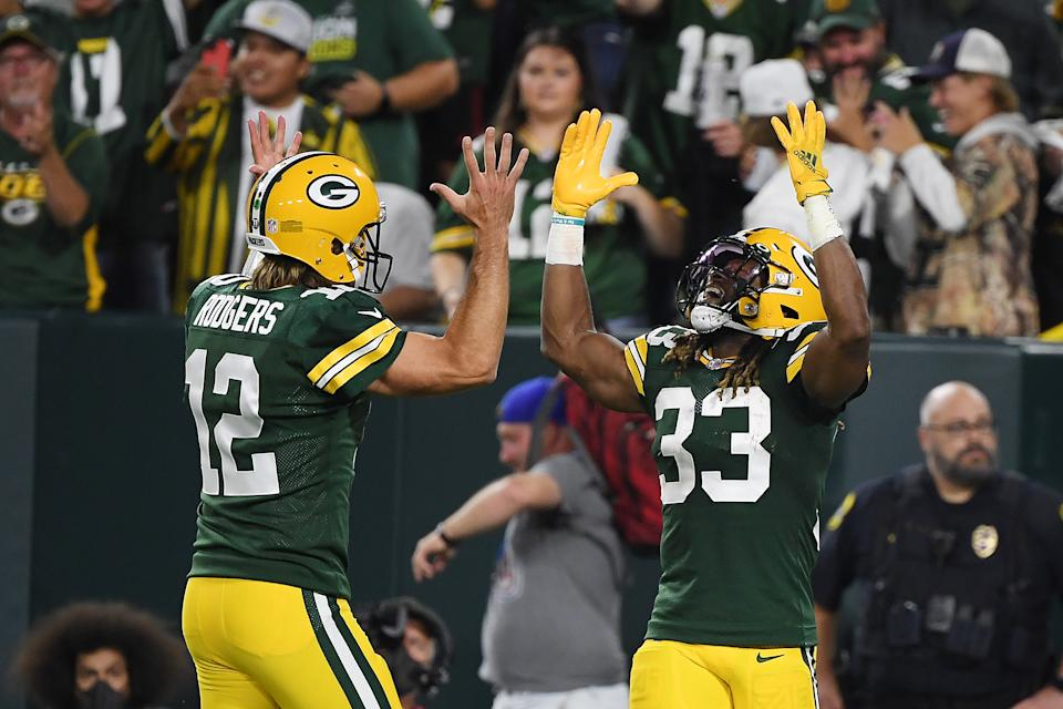 GREEN BAY, WISCONSIN - SEPTEMBER 20: Aaron Jones #33 of the Green Bay Packers celebrates a touchdown against the Detroit Lions with teammate Aaron Rodgers #12 during the first half at Lambeau Field on September 20, 2021 in Green Bay, Wisconsin. (Photo by Quinn Harris/Getty Images)