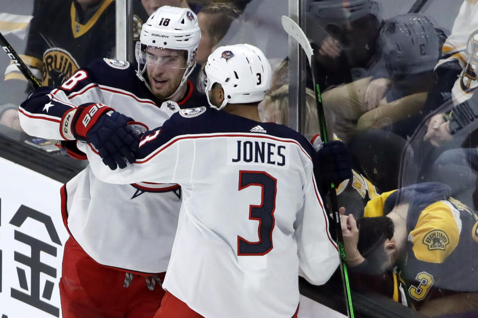 Columbus Blue Jackets center Pierre-Luc Dubois (18) celebrates his winning goal against the Boston Bruins with teammate Seth Jones (3) in the overtime period of an NHL hockey game, Thursday, Jan. 2, 2020, in Boston. (AP Photo/Elise Amendola)