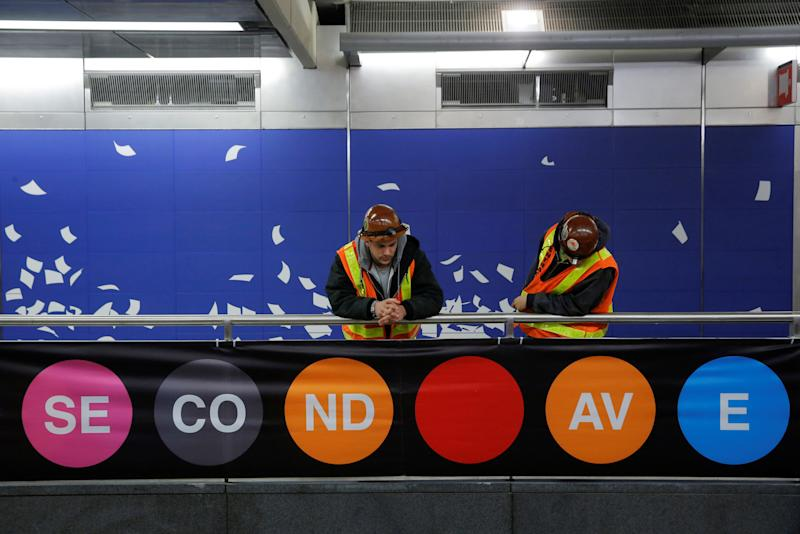 Workers Ryan Walker and Michael Grund peer over onto the platform at the 96th Street Station during a preview event for the Second Avenue subway line in Manhattan, New York City, U.S., December 22, 2016. REUTERS/Andrew Kelly