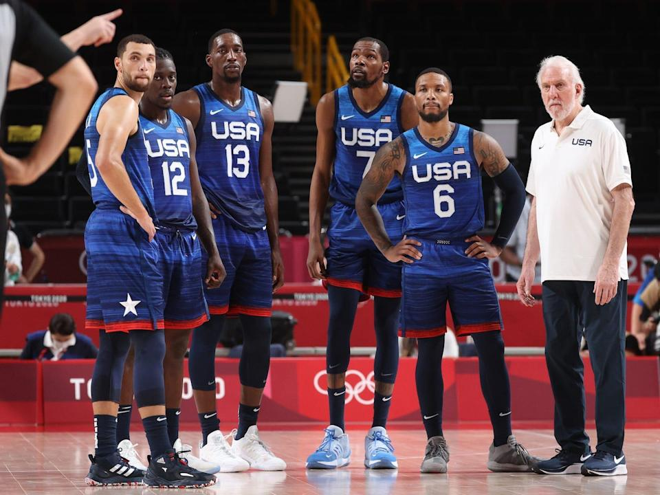 Zach LaVine, Jrue Holiday, Bam Adebayo, Kevin Durant, Damian Lillard, and Gregg Popovich stand during a basketball game at the Tokyo Olympics.
