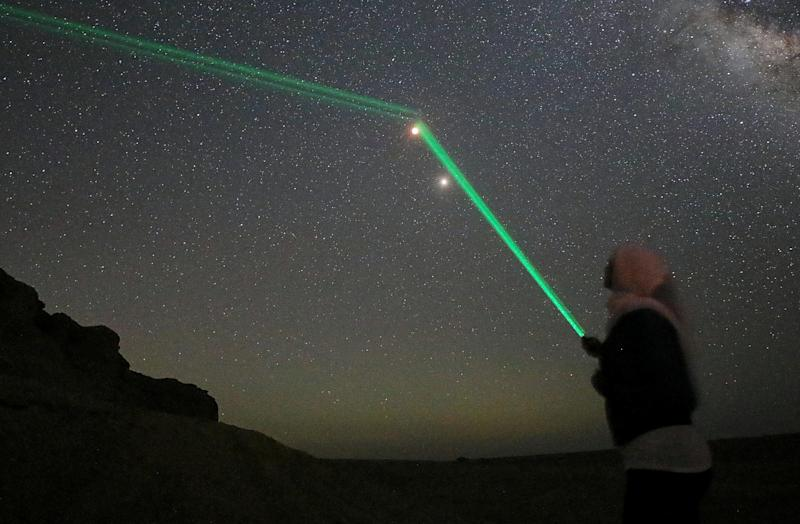 People shine laser lights towards the moon in the desert of Al Fayoum Governorate, south-west of Cairo, Egypt. (Mohamed Abd El Ghany / Reuters)