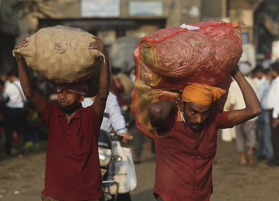 Laborers carry vegetables in Mumbai, India, Wednesday, Dec. 30, 2020. India's confirmed coronavirus cases have crossed 10 million with new infections dipping to their lowest levels in three months, as the country prepares for a massive COVID-19 vaccination in the new year. (AP Photo/Rafiq Maqbool)