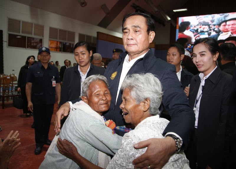 In this March 13, 2019, photo, elderly locals hug Prime Minister Prayuth Chan-ocha and candidate for the same position, as he attends a government-sponsored event in Nakhon Ratchasima, Thailand. Prayuth has been nominated by a pro-army political party to become prime minister again after the March 24 general election. (AP Photo/Sakchai Lalit)