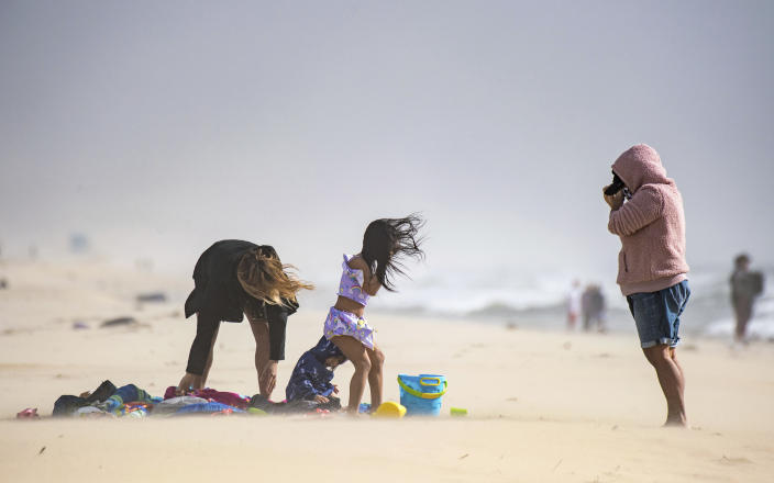 Marich Schapiro, left, her daughters, Cassie Schapiro and AJ Schapiro, and June Castillo, brave the wind as they wait for Schapiro's husband to finish surfing south of the pier in Huntington Beach, Calif., on Tuesday, Jan. 19, 2021. (Jeff Gritchen/The Orange County Register/SCNG via AP)