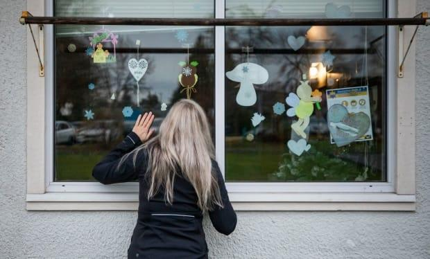 A woman waves to her brother through his window at the George Pearson extended care facility in Vancouver in December, 2020. As of April 1, 2021, rules for visitors at long term care facilities are being relaxed to allow more visitors, and contact with residents. (Ben Nelms/CBC - image credit)