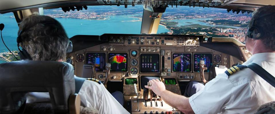 The cockpit of modern jet airplane. Aircraft flies above the city landscape and river. Pilots at work.