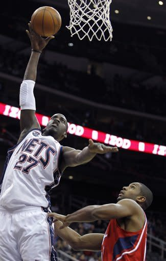 New Jersey Nets' Johan Petro (27), of France, goes up for a shot against Atlanta Hawks' Al Horford, right, in the first quarter of an NBA basketball game, Monday, Jan. 9, 2012, in Newark, N.J. (AP Photo/Julio Cortez)
