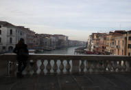 """FILE - In this Jan. 30, 2021 file photo, a woman looks the Canal Grande or Grand Canal, in Venice, Italy. The canal city's Carnival festivities should have started on Jan. 30, but the COVID-19 pandemic made the annual appointment for more than two weeks of merry-making impossible. Venice's central place in the history of battling pandemics and pestilence will come into focus at this year's Venice Film Festival, which opens Wednesday with the premiere of Pedro Almodovar's in-competition """"Madres Paralelas"""" (Parallel Mothers), which he developed during Spain's 2020 coronavirus lockdown, one of the harshest in the West. (AP Photo/Antonio Calanni)"""