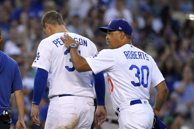 Los Angeles Dodgers right fielder Joc Pederson gets a pat on the back from manager Dave Roberts as he leaves the game after colliding with the wall while making a catch on a ball hit by Colorado Rockies' Charlie Blackmon during the fifth inning of a baseball game Monday, Sept. 2, 2019, in Los Angeles. (AP Photo/Mark J. Terrill)