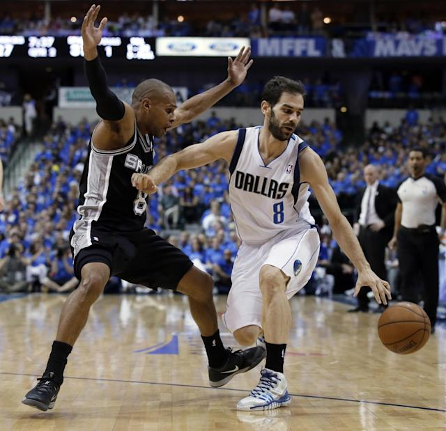 San Antonio Spurs' Patty Mills, left, is knocked back by Dallas Mavericks' Jose Calderon as Calderon loses control of the dribble in the first half of Game 4 of an NBA basketball first-round playoff series, Monday, April 28, 2014, in Dallas. (AP Photo/Tony Gutierrez)