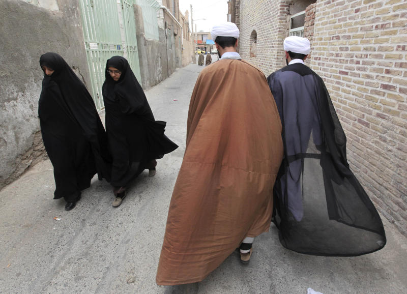 In this picture taken on Tuesday, May 6, 2013, two Iranian clerics, right, and two women walk in an alley of the eastern city of Birjand, Iran. When struggling families in the eastern Iranian city of Birjand take measure of Mahmoud Ahmadinejad's presidency in its waning weeks, it's not about his browbeating oratory against the West or his battles with Iran's ruling clerics. Instead, it's the rows of simple two-story homes on the city's outskirts that sharply improved their lives. (AP Photo/Vahid Salemi)
