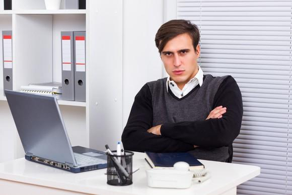 An upset young man with his arms crossed, sitting in front of his laptop.