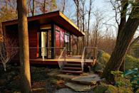 """<p>Set in a wooded area, this 300-square-foot studio retreat in Chappaqua, New York, is nestled between two rock outcroppings—one is used as a backdrop and the other as a bookend to the deck. The design team at <a href=""""http://www.workshopapd.com/"""" rel=""""nofollow noopener"""" target=""""_blank"""" data-ylk=""""slk:Workshop/APD"""" class=""""link rapid-noclick-resp"""">Workshop/APD</a> chose Dark Ipe siding and decking and walnut interiors for a natural mid-century modern look that connects the structure to its wooded surroundings. Windows wrapping the western facade frame the scenery and visually enlarge the intimate space.</p><p><a class=""""link rapid-noclick-resp"""" href=""""http://www.workshopapd.com/portfolio/residential/studio-retreat"""" rel=""""nofollow noopener"""" target=""""_blank"""" data-ylk=""""slk:SEE INSIDE"""">SEE INSIDE</a></p>"""