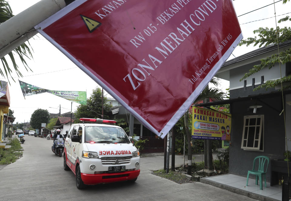 """An ambulance carrying the body of a COVID-19 victim drives past a sign that reads """"COVID-19 Red Zone,"""" on its way to a cemetery for burial in Bekasi on the outskirts of Jakarta, Indonesia, July 11, 2021. Indonesia surpassed the grim milestone of 100,000 official COVID-19 deaths on Wednesday, Aug. 4, 2021, as the country struggles with its worst pandemic year fueled by the delta variant, with growing concerns that the actual figure could be much higher with people also dying at home. (AP Photo/Achmad Ibrahim)"""