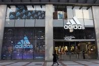 Woman walks past an Adidas store at a shopping mall in Beijing