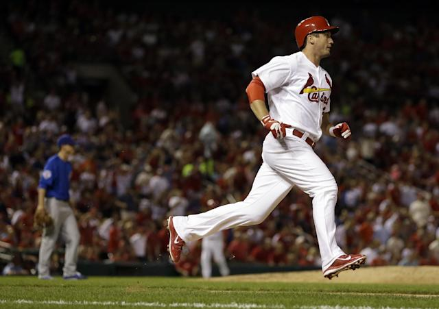 St. Louis Cardinals' David Freese, right, rounds the bases after hitting a solo home run off Chicago Cubs relief pitcher Brooks Raley, left, during the third inning of a baseball game, Friday, Sept. 27, 2013, in St. Louis. (AP Photo/Jeff Roberson)