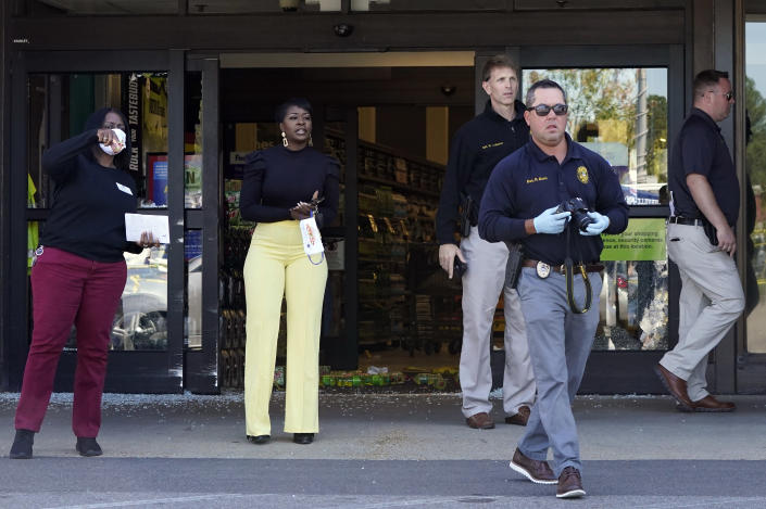Police officers and Kroger employees exit a Kroger grocery store Friday, Sept. 24, 2021, in Collierville, Tenn. Police say a gunman, who has been identified as a third-party vendor to the store, attacked people Thursday and killed at least one person and wounded others before being found dead of an apparent self-inflicted gunshot wound. (AP Photo/Mark Humphrey)