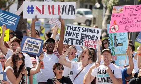 "FILE PHOTO: Students hold signs while rallying in the street during the ""March for Our Lives"" demanding stricter gun control laws at the Miami Beach Senior High School, in Miami, Florida, U.S., March 24, 2018.  REUTERS/Javier Galeano/File Photo"