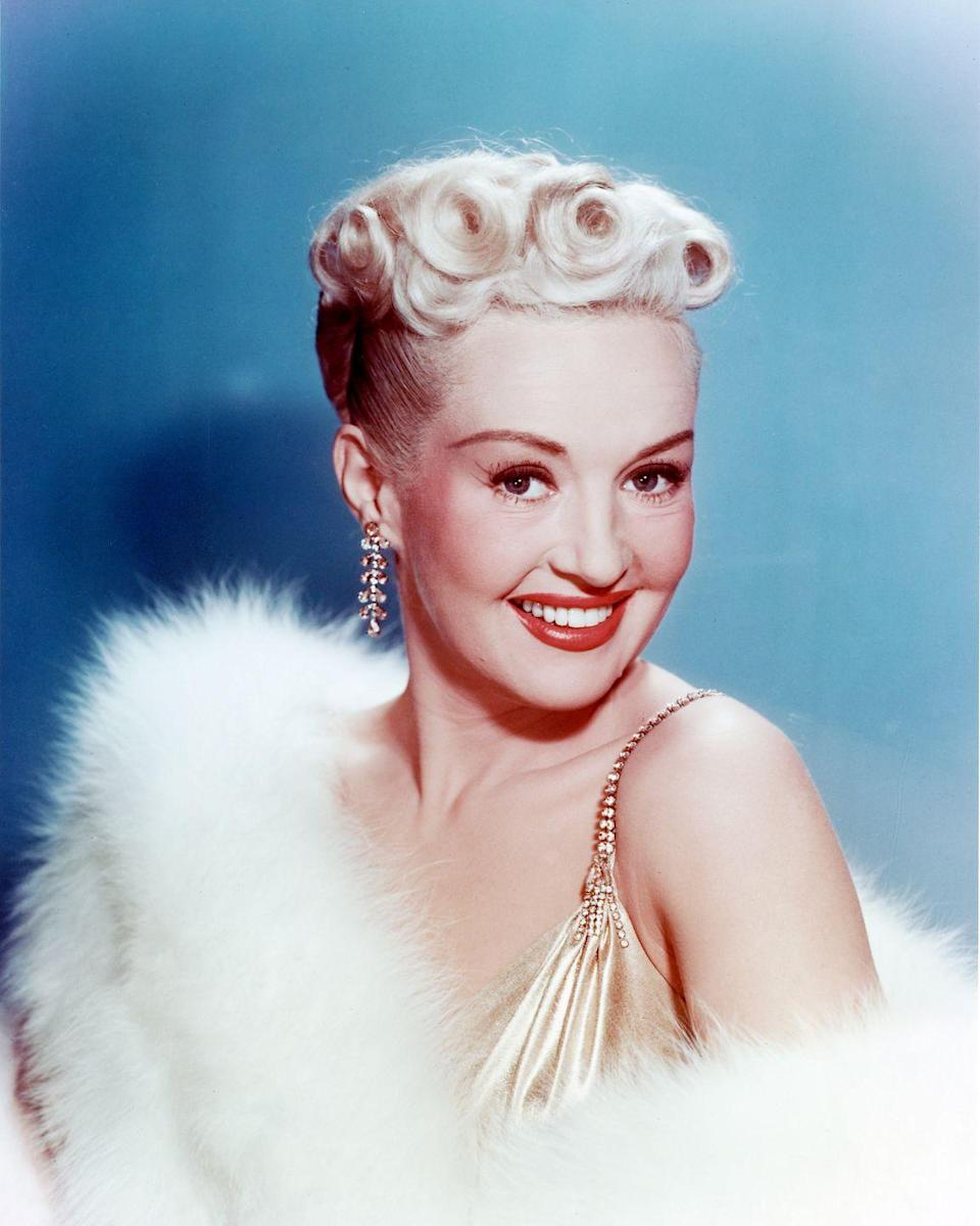 """<p>Not content to keep things basic, stars like Betty Grable brought pin curls and finger waves to the next level with bold blonde hair, <a href=""""http://www.goodhousekeeping.com/beauty/makeup/g2771/best-red-lipstick-for-all-skin-tones/"""" rel=""""nofollow noopener"""" target=""""_blank"""" data-ylk=""""slk:red lipstick"""" class=""""link rapid-noclick-resp"""">red lipstick</a>, and fun fashion.</p>"""