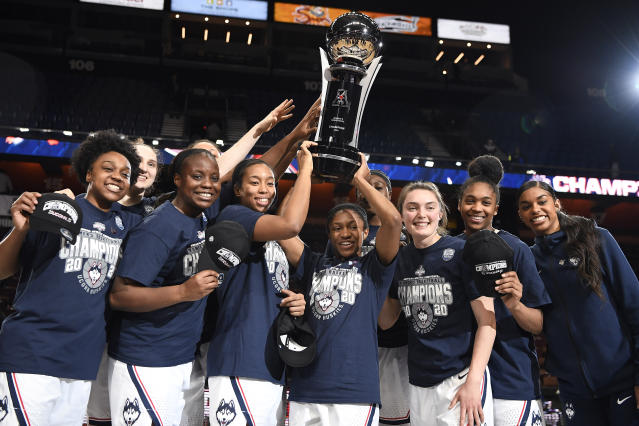 Connecticut players hold up the American Athletic Conference championship trophy the end of an NCAA college basketball game against Cincinnati in the American Athletic Conference tournament finals at Mohegan Sun Arena, Monday, March 9, 2020, in Uncasville, Conn. (AP Photo/Jessica Hill)