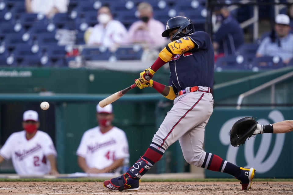 Atlanta Braves' Ronald Acuna Jr. hits a fielder's choice ground ball in the seventh inning of an opening day baseball game against the Washington Nationals at Nationals Park, Tuesday, April 6, 2021, in Washington. Austin Riley scored on the play. (AP Photo/Alex Brandon)