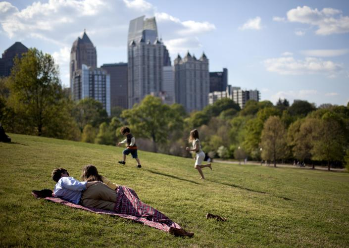 FILE - In this March 25, 2012, file photo a couple enjoy a sunny afternoon against the backdrop of the Midtown skyline from Piedmont Park in Atlanta. The lower 48 states were 8.6 degrees above normal for March and 6 degrees higher than average for the first three months of the year, according to calculations by the National Oceanic and Atmospheric Administration, with both March and the first three months of the year far exceeding the country's old records.(AP Photo/David Goldman)