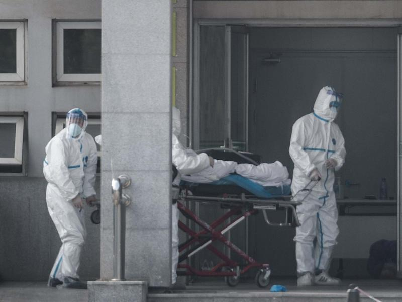 Medical staff carry a patient into the Jinyintan hospital, where patients infected with a new strain of Coronavirus identified as the cause of the Wuhan pneumonia outbreak are being treated: EPA