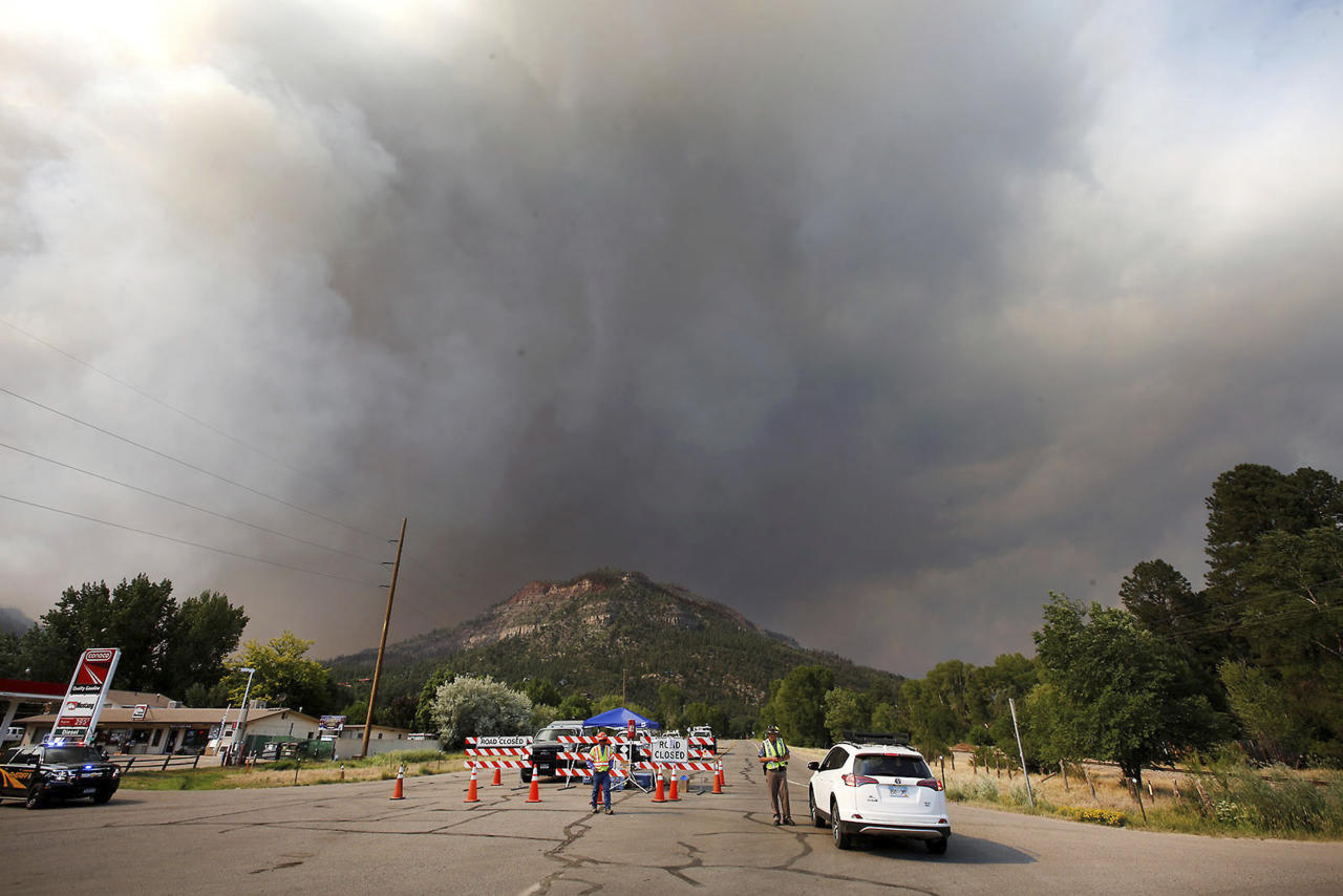 <p>Smoke rises from the 416 Fire behind the U.S. Highway 550 road block at Cometti Lane on Wednesday, June 13, 2018, near Durango, Colo. (Photo: Jerry McBride/The Durango Herald via AP) </p>