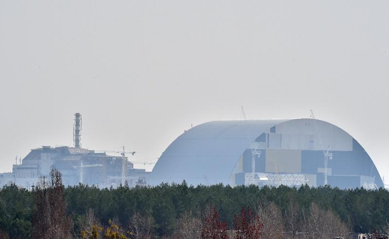 The fourth block of Chernobyl's Nuclear Power Plant (L) and Chernobyl's New Safe Confinement arch (R) pictured on April 8, 2016 (AFP Photo/Sergei Supinsky)