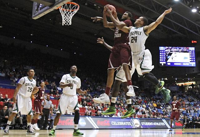 Texas Southern forward D'Angelo Scott (15) goes up for a rebound against Cal Poly guard Jamal Johnson (24) in the first half of a first-round game of the NCAA college basketball tournament on Wednesday, March 19, 2014, in Dayton, Ohio. (AP Photo/Skip Peterson)