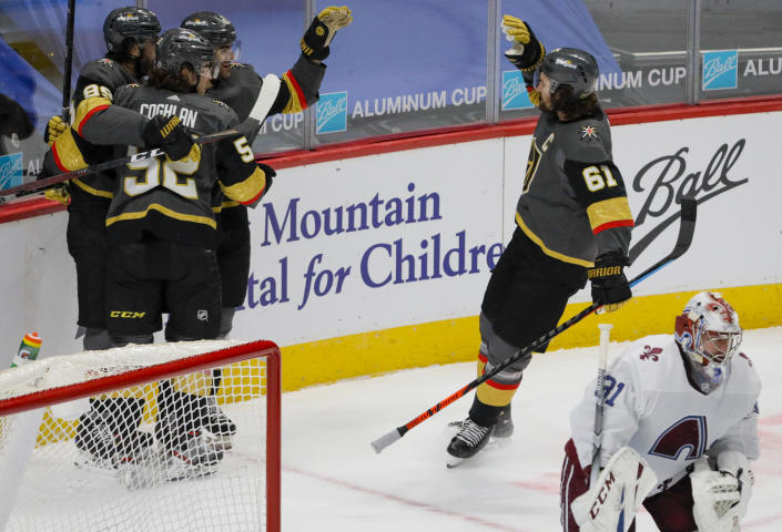Vegas Golden Knights right wing Alex Tuch (89) and defenseman Dylan Coghlan (52) hug Golden Knights left wing Max Pacioretty (67) as right wing Mark Stone (61) high-fives him after Pacioretty scored the winning goal in overtime against Colorado Avalanche goaltender Philipp Grubauer (31) during an NHL hockey game in Denver, Saturday, March 27, 2021. (AP Photo/Joe Mahoney)